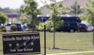 FILE - In this May 25, 2018, file photo, Law enforcement vehicles are seen behind a school sign after a shooting at Noblesville West Middle School in Noblesville, Ind. The 13-year-old boy who opened fire inside the school, wounding a classmate and a teacher before being tackled by the teacher, was expected to learn his punishment on Wednesday, Nov. 14, 2018. (Robert Scheer/The Indianapolis Star via AP, File)