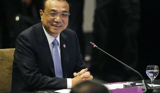 Chinese Premier Li Keqiang smiles as he glances at ASEAN leaders after delivering his statement at the ASEAN Plus China Summit in the ongoing 33rd ASEAN Summit and Related Summits Wednesday, Nov. 14, 2018 in Singapore. China's premier sought Tuesday to reassure its neighbors that Beijing will push ahead with reforms needed to support growth across the region and also keep the peace in contested waters in the South China Sea. (AP Photo/Bullit Marquez)