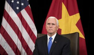 U.S. Vice President Mike Pence listens to Vietnam's Prime Minister Nguyen Xuan Phuc, not seen, in Singapore, Wednesday, Nov. 14, 2018. Pence is Singapore to attend the 33rd ASEAN summit. (AP Photo/Bernat Armangue, Pool)
