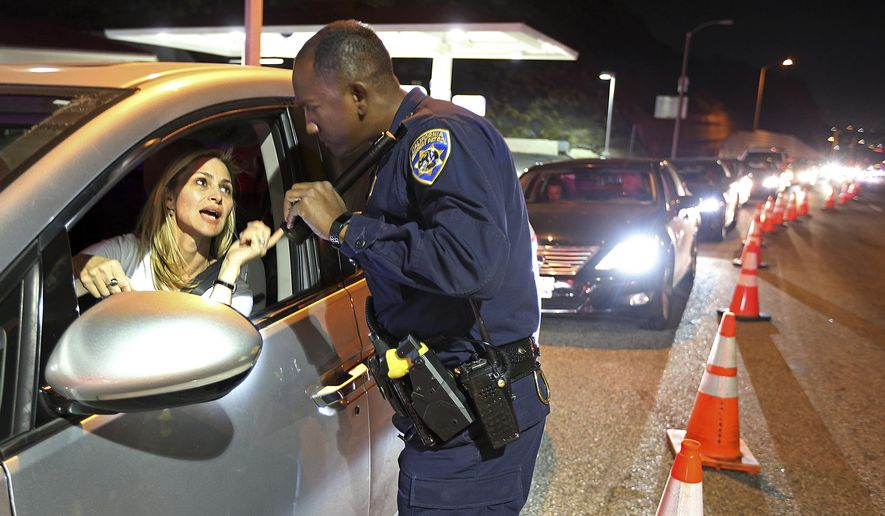 California Highway patrol Officer S. Kizito verifies that a woman seeking to return to Malibu in Southern California is an actual resident after Woolsey Fire evacuation orders were lifted for the eastern portion of the city Tuesday evening, Nov. 13, 2018. (AP Photo/Reed Saxon)