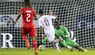Qatar's Akram Afif, center, scores his side's opening goal past Switzerland's Kevin Mbabu, left, and goalkeeper Yvon Mvogo during an international friendly soccer match between Switzerland and Qatar at the Cornaredo stadium in Lugano, Switzerland, Wednesday, Nov. 14, 2018. (Ennio Leanza/Keystone via AP)