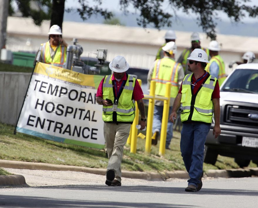 FILE - In this June 26, 2018, file photo, construction workers leave a temporary entrance to Coryell Memorial Healthcare System hospital where an explosion in a building under construction injured several people, and knocked power out for a large portion of the city in Gatesville, Texas. Investigators say an explosion that killed three people and injured 13 others at the Texas hospital earlier this year was caused by natural gas that leaked into a boiler room and an adjacent mechanical room. (Rod Aydelotte/Waco Tribune-Herald via AP, File)