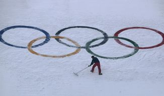 """FILE - In this Feb. 10, 2018, file photo, a worker grooms the snow after installing a set of Olympic Rings on the ski jump hill at the 2018 Winter Olympics at the Alpensia Ski Jumping Center in Pyeongchang, South Korea. Does anyone really want to host the Winter Olympics? Residents in Calgary answered that question with a resounding """"No,"""" and now the International Olympic Committee has some soul-searching to do. (AP Photo/Charlie Riedel, File)"""