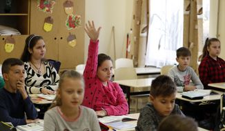 In this Friday, Oct. 19, 2018, file photograph, children attend class at the Velyka Dobron High School in Velyka Dobron, Ukraine. (AP Photo/Laszlo Balogh)