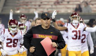 In this Nov. 3, 2018, file photo, Southern California head coach Clay Helton leads his team onto the field before an NCAA college football game in Corvallis, Ore. Helton has told his players not to worry about his job security as they head into the final two games of their 5-5 regular season. Helton realizes fans are unhappy just one season after he led the Trojans to the Pac-12 title.  (AP Photo/Timothy J. Gonzalez, File)