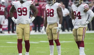 FILE - In this Oct. 28, 2018, file photo, San Francisco 49ers' DeForest Buckner (99), Ronald Blair III (98) and Solomon Thomas (94) wait for a play against the Arizona Cardinals during the first half of an NFL football game in Glendale, Ariz. Thomas, the No. 3 overall pick in the 2017 draft, has struggled even to get onto the field in pass-rushing situations. He lacks the speed to come off the edge and hasn't shown the ability to be one of the team's top inside rushers so he has been mostly relegated to being only a base defender. (AP Photo/Darryl Webb, File)