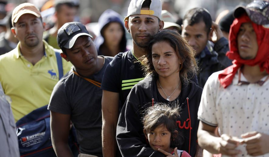 Marvin Ochoa, center, of Honduras, waits in line for a meal behind his wife Diana Marylin Ochoa after they arrived with a Central America migrant caravan to Tijuana, Mexico, Thursday, Nov. 15, 2018. Members of the migrant caravan started to meet some local resistance as they continued to arrive by the hundreds in the Mexican border city of Tijuana, where a group of residents clashed with migrants camped out by the U.S. border fence. (AP Photo/Gregory Bull)