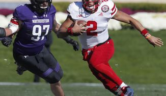 FILE - In this Oct. 13, 2018, file photo, Nebraska's Adrian Martinez, right, runs upfield past Northwestern's Joe Gaziano during the first half of an NCAA college football game, in Evanston, Ill. Martinez leads a Nebraska offense that has gone over 450 yards of total offense in seven straight games for the first time in program history. (AP Photo/Jim Young, File)