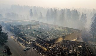 Smoke hangs over the scorched remains of Old Town Plaza following the wildfire in Paradise, Calif., on Thursday, Nov. 15, 2018. The shopping center housed a Safeway and other businesses. (AP Photo/Noah Berger)