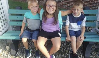 FILE - This undated family file photo provided by Elgin Ingle shows Alivia Stahl, center, and her twin brothers, Xzavier and Mason Ingle. The three children were struck and killed Tuesday, Oct. 30, 2018, by a pickup truck as they crossed a road in rural Rochester, Ind., to board a school bus before sunrise. The driver of the pickup Alyssa Shepherd, of Rochester, who is scheduled to appear Thursday, Nov. 15, 2018, was arrested and charged with three counts of reckless homicide and one misdemeanor count of passing a school bus when arm signal device is extended, causing bodily injury. (Elgin Ingle via AP, File)