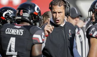 FILE - In this Saturday, Nov. 3, 2018, file photo, Cincinnati head coach Luke Fickell, right, speaks with linebacker Malik Clements (4) before an NCAA college football game against Navy in Cincinnati. No. 19 Cincinnati is in contention for the American Athletic title at it prepares to play at 11th-ranked and undefeated UCF on Saturday.(AP Photo/John Minchillo, File)