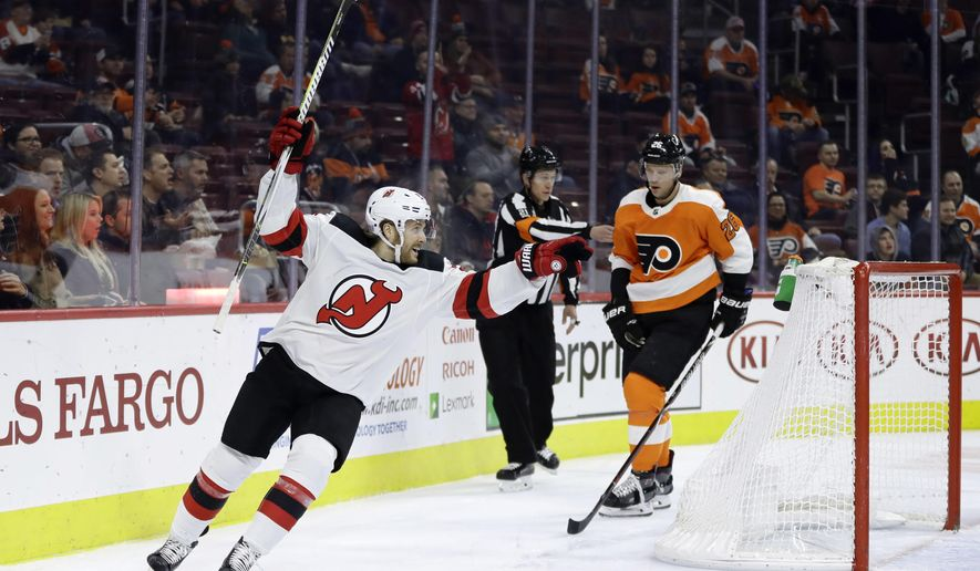 New Jersey Devils' Blake Coleman, left, reacts past Philadelphia Flyers' Christian Folin after a goal by Joey Anderson during the first period of an NHL hockey game, Thursday, Nov. 15, 2018, in Philadelphia. (AP Photo/Matt Slocum)