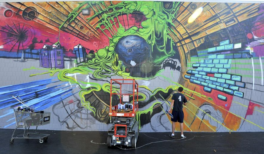 In this Oct. 8, 2018 photo, Bradley University student Mike Brown works on a mural  on the Unclaimed Freight store in Peoria, Ill. The new mural on the UFS Downtown Outlet Center is the largest piece of art the Bradley student has ever created. The brightly colored 20-foot by 50-foot mural draws upon Brown's love for science fiction and graffiti. (Leslie Renken/Journal Star via AP)