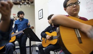 Jesse De Los Santos guitar teacher at Miller High School checks with is Metro Middle School students as they learn a new song his first pried class on Wednesday, Sept. 26, 2018. De Los Santos is the guitarist in the local band Blind Owls.  (Courtney Sacco/Corpus Christi Caller-Times via AP)