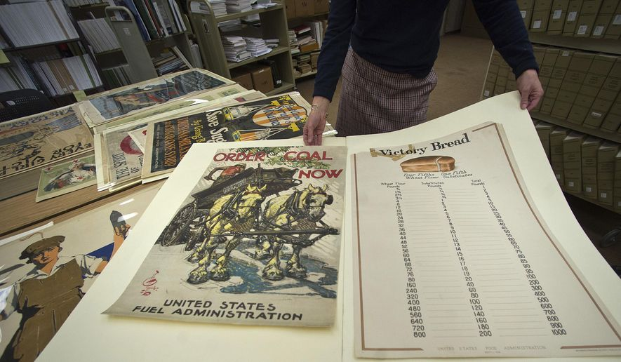 In this Nov. 7, 2018 photo, Angela Bonnell, head of government documents at Illinois  State University's Milner Library, shows a World War I-era poster from the United States Food Administration, in Normal, Illinois. The posters promoted the rationing of sugar as part of the war effort. (Lewis Marien/The Pantagraph via AP)