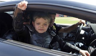 In this file photo from Tuesday, April 8, 2014, Miles Scott, dressed as Batkid, gestures as he sits in the Batmobile after throwing the ceremonial first pitch before a baseball game between the San Francisco Giants and the Arizona Diamondbacks in San Francisco. On the five-year anniversary of then-5-year-old Miles Scott capturing the hearts of millions by saving the day in San Francisco as Batkid, his Make-A-Wish Foundation dream accomplished at last, the fifth-grader is thriving. (AP Photo/Eric Risberg, Pool)