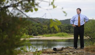 FILE - In this July 16, 2009, file photo, Oklahoma Attorney General Drew Edmondson stands by the Illinois river in Tahlequah, Okla., when he sued 12 Arkansas poultry companies for polluting the Illinois River watershed. Conservation groups are expressing disappointment with an agreement between Oklahoma and Arkansas officials to study ways to improve water quality in the Illinois River watershed. The groups say the agreement fails to control pollution of the river in Oklahoma and merely calls for another study of the river's basin. (AP Photo/Brandi Simons, File)