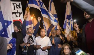 Israeli protesters hold flags during a demonstration against the cease-fire between Israel and Gaza's Hamas in the southern Israeli city of Ashkelon, Wednesday, Nov. 14, 2018. Israel's defense minister on Wednesday abruptly resigned to protest a new cease-fire with Hamas militants in Gaza, throwing the government into turmoil and pushing the country toward an early election. (AP Photo/Tsafrir Abayov)