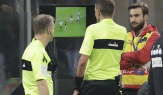 Referee Paolo Silvio Mazzoleni, center checks the VAR during a Serie A soccer match between AC Milan and Juventus, at Milan's San Siro stadium, Sunday, Nov. 11, 2018. (AP Photo/Luca Bruno)