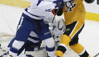 Pittsburgh Penguins' Patric Hornqvist (72) works against Tampa Bay Lightning's Anthony Cirelli (71) in front of Lightning goalie Louis Domingue during the first period of an NHL hockey game in Pittsburgh, Thursday, Nov. 15, 2018. (AP Photo/Gene J. Puskar)