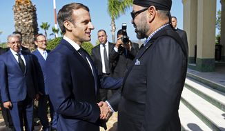 French President Emmanuel Macron, left, is welcomed by Moroccan King Mohammed VI at Tangiers' airport, Morocco, Thursday, Nov. 15, 2018. Macron and Morocco's King Mohammed VI are inaugurating Morocco's first high-speed rail line, the first ever such line in Africa. (Christophe Archambault, Pool via AP)