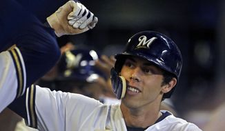 FILE - In this Monday, Sept. 17, 2018 file photo, Milwaukee Brewers' Christian Yelich is congratulated by teammates in the dugout after hitting a two-run home run during the fifth inning of a baseball game against the Cincinnati Reds in Milwaukee. Milwaukee outfielder Christian Yelich was a runaway winner for the National League Most Valuable Player award after helping the Brewers return to the playoffs for the first time in seven years. Yelich received 29 first-place votes and 415 points from the Baseball Writers' Association in balloting announced Thursday, Nov. 15, 2018. (AP Photo/Aaron Gash, File) **FILE**