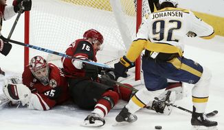 Arizona Coyotes goaltender Darcy Kuemper (35) gets some help from Coyotes center Brad Richardson (15) on a shot by Nashville Predators center Ryan Johansen (92) during the second period of an NHL hockey game Thursday, Nov. 15, 2018, in Glendale, Ariz. (AP Photo/Ross D. Franklin)