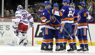 New York Islanders' Anthony Beauvillier, third from left, celebrates with teammates after scoring a goal as New York Rangers goaltender Henrik Lundqvist (30) stands in front of the goal during the first period of an NHL hockey game Thursday, Nov. 15, 2018, in New York. (AP Photo/Frank Franklin II)