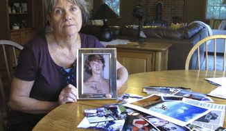 In this Oct. 9, 2018 photo, Linda Marino poses with photographs of her son, Samuel, at her home in Tolland, Conn. Samuel Marino died in a 2009 car crash that relatives believe was intentional after becoming a victim of a male sex trafficking ring. Advocates are calling for more recognition and services for male victims. (AP Photo/Dave Collins)