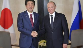 Russian President Vladimir Putin, right, and Japanese Prime Minister Shinzo Abe pose for a photo during the ASEAN-Russia Summit in the ongoing 33rd ASEAN Summit and Related Summits Wednesday, Nov. 14, 2018 in Singapore. (Alexei Druzhinin, Sputnik, Kremlin Pool Photo via AP)