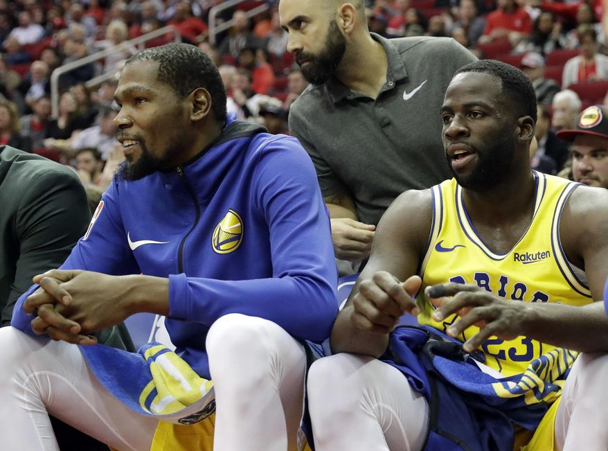 Golden State Warriors' Kevin Durant, left, and Draymond Green sit on the bench during the first half of an NBA basketball game against the Houston Rockets Thursday, Nov. 15, 2018, in Houston. (AP Photo/David J. Phillip)