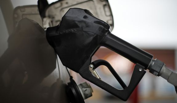This is a gas pump nozzel in a car filling up at a pump in West Mifflin, Pa., on Friday, Nov. 16, 2018. (AP Photo/Gene J. Puskar)