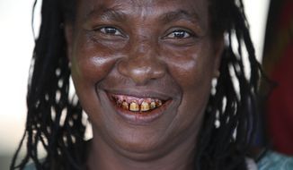 In this Thursday, Nov. 15, 2018, photo, Margaret John smiles as she sells betel nut at the Koki Buai market at Port Moresby, Papua New Guinea. Along with drinking alcohol in public places, chewing betel nut and spitting out the messy remains, has been aggressively discouraged in Port Moresby this year. It's part attempt to literally clean up the coastal city of 300,000 as world leaders briefly descend on it for a APEC summit this weekend and part the latest episode of an ongoing struggle to control betel nut after previous attempts to completely ban it in the city caused chaos. (AP Photo/Aaron Favila)