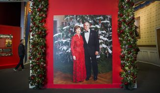 "A photo of President George W. Bush and Laura Bush  is displayed at a Christmas exhibit at The George W. Bush Presidential Center and Library on Thursday, Nov. 15, 2018 on the SMU campus in Dallas. The exhibit, called ""Deck the Halls and Welcome All: Christmas at the White House 2006,"" opened Thursday and runs through Jan. 6.  (Ashley Landis /The Dallas Morning News via AP)"