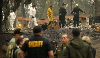 Investigators recover human remains at a home burned in the Camp Fire, Thursday, Nov. 15, 2018, in Magalia, Calif. Many of the missing in the deadly Northern California wildfire are elderly residents in Magalia, a forested town of about 11,000 north of the destroyed town of Paradise. (AP Photo/John Locher)