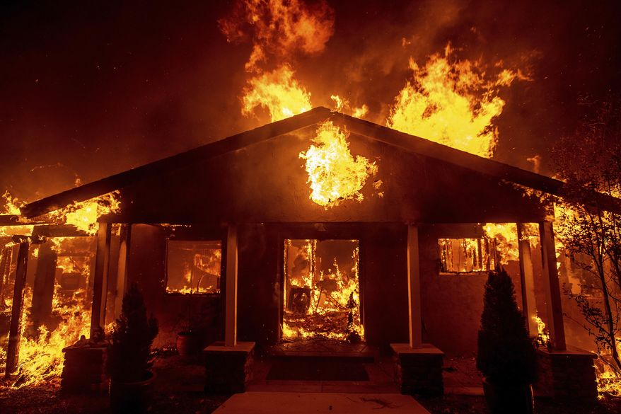 FILE - In this Thursday, Nov. 8, 2018 file photo, a home burns as the Camp Fire rages through Paradise, Calif. This town of 27,000 was destroyed in the deadliest, most destructive wildfire in California history. And memories are all that's left for many of the survivors. They recall a friendly place where the pace was relaxed, where families put down roots and visitors opted to stay. (AP Photo/Noah Berger)