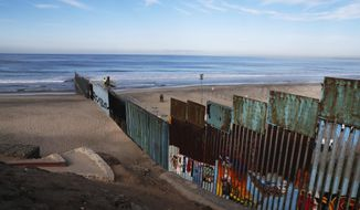 U.S. Border Patrol agents observe as workers place concertina wire on the border structure Separating Mexico and the United States, where the border meets the Pacific Ocean, Friday, Nov. 16, 2018. (AP Photo/Marco Ugarte) ** FILE **