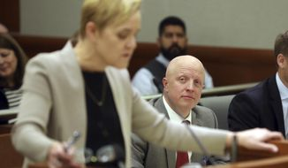 Robert P. Harrington, seated in background, who represents Republican U.S. Rep. Mia Love's lawsuit, looks on as Deputy Salt Lake County attorney Bridget K. Romano, foreground, speaks in Third District Court, Thursday Nov. 15, 2018, in West Jordan, Utah. A Utah judge has reserved a decision on a lawsuit in a tight House race filed by a Republican incumbent who is seeking to halt vote counting in a Democratic-leaning county that's key to the outcome. Judge James Gardner heard arguments Thursday in the lawsuit filed by U.S. Rep Mia Love, but ended the hearing without making a ruling. (AP Photo/Rick Bowmer, Pool)
