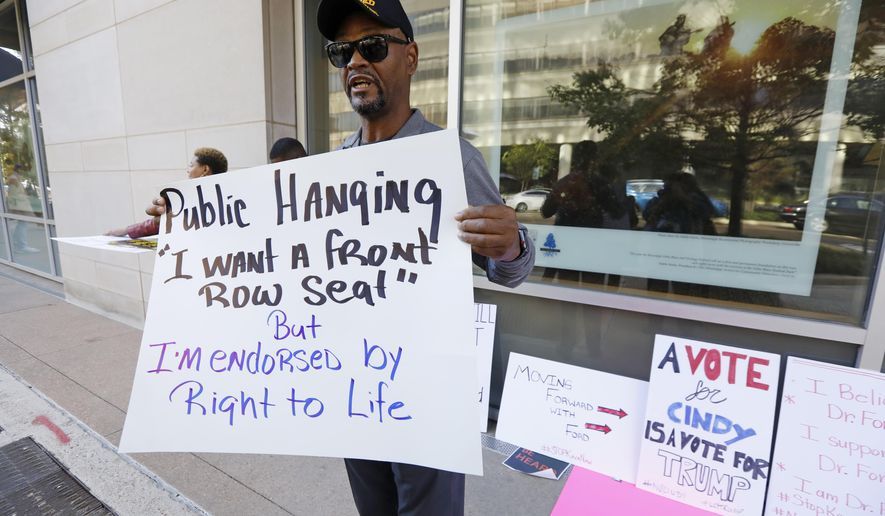 """George H. Williams of Ridgeland, Miss., holds a protest sign outside the downtown complex that houses the offices of appointed U.S. Sen. Cindy Hyde-Smith, R-Miss., on Friday, Nov. 16, 2018, in Jackson, Miss. Williams, a Marine Corps veteran, said he was upset with comments Hyde-Smith made about """"public hanging"""" and voting rights. Hyde-Smith and Democrat Mike Espy are competing to serve the final two years of a six-year term started by Republican Thad Cochran, who retired. (AP Photo/Rogelio V. Solis)"""