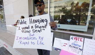 "George H. Williams of Ridgeland, Miss., holds a protest sign outside the downtown complex that houses the offices of appointed U.S. Sen. Cindy Hyde-Smith, R-Miss., on Friday, Nov. 16, 2018, in Jackson, Miss. Williams, a Marine Corps veteran, said he was upset with comments Hyde-Smith made about ""public hanging"" and voting rights. Hyde-Smith and Democrat Mike Espy are competing to serve the final two years of a six-year term started by Republican Thad Cochran, who retired. (AP Photo/Rogelio V. Solis)"