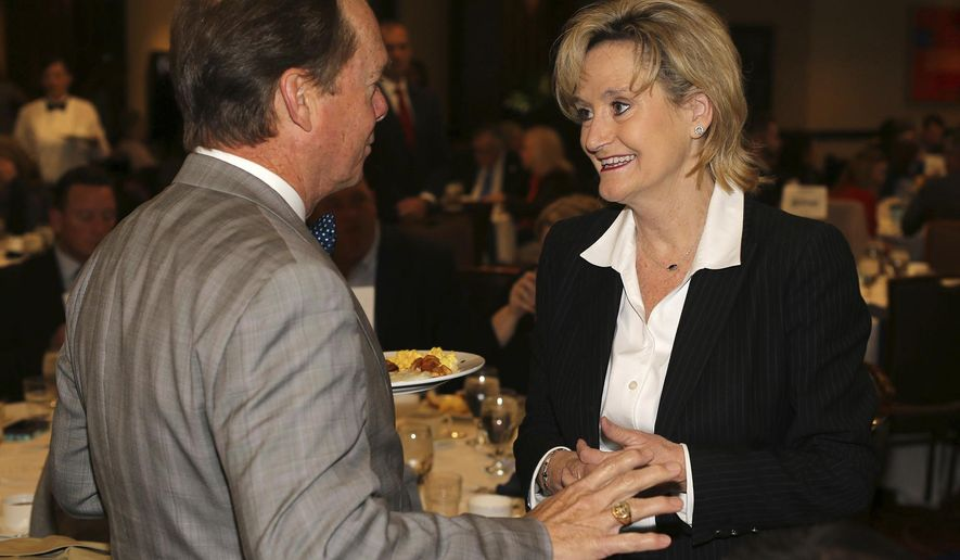 Senator Cindy Hyde-Smith, R-Miss., talks to Gulfport Mayor Billy Hewes at a Gulf Coast Business Council meeting at the IP Casino Resort Spa in Biloxi, Miss., on Friday, Nov. 16, 2018. Hyde-Smith is in a runoff with Democrat Mike Espy to retain her Senate seat. (AP Photo/Sun Herald, John Fitzhugh)/The Sun Herald via AP)
