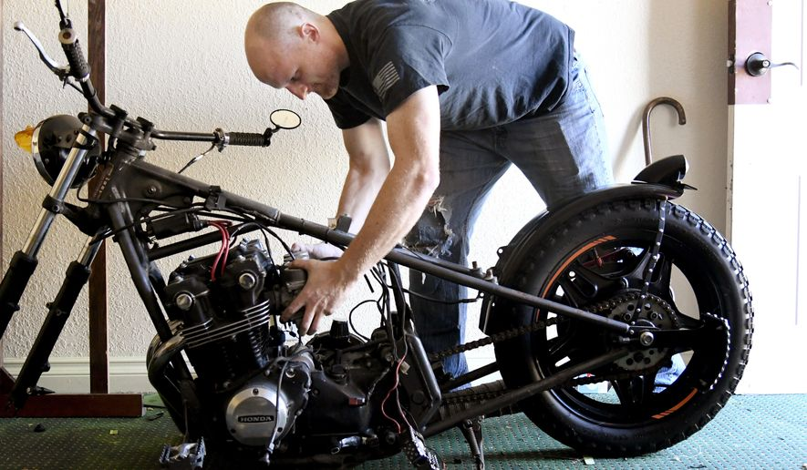 In this Nov. 3, 2018 photo, U.S. Army veteran Jason Cormier takes the carburetor off his custom 1981 Honda 750 motorcycle at the Home Port Veterans Transition Home in Macon, Ga. Cormier's house was foreclosed on after he and his wife divorced after his final deployment. Cormier is currently living at the Transition Home while majoring in interdisciplinary studies at Middle Georgia State University. (Jason Vorhees/The Macon Telegraph via AP)