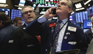 FILE- In this Nov. 8, 2018, file photo traders Eric Schumacher, left, and Richard Deviccaro work on the floor of the New York Stock Exchange. The U.S. stock market opens at 9:30 a.m. EDT on Friday, Nov. 16. (AP Photo/Richard Drew, File)