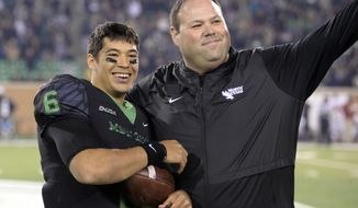 North Texas quarterback Mason Fine (6) stands next to the school's athletic director, Wren Baker, after Fine received a game ball at the team's NCAA college football game against Florida Atlantic on Thursday, Nov. 15, 2018, in Denton, Texas. (Jake King/The Denton Record-Chronicle via AP)