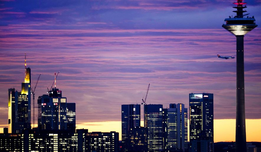 An aircraft flies over the bank buildings and the television tower before sunrise in Frankfurt, Germany, Monday, Nov. 12, 2018. (AP Photo/Michael Probst)