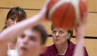 German Chancellor Angela Merkel, right, attends the training of the NINERS German first divisioner basketball youth teams (under 16 years and under 19 years) during her one-day visit in Chemnitz, eastern Germany, Friday, Nov. 16, 2018. Chemnitz has seen a few federal politicians show their faces since a 35-year-old local man was stabbed to death in August, allegedly by migrants, followed by a surge of violent right-wing protests. (AP Photo/Jens Meyer)