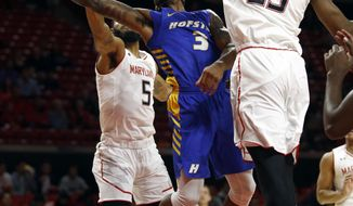 Hofstra guard Justin Wright-Foreman, center, is fouled by Maryland guard Eric Ayala (5) as he shoots between Ayala and Maryland forward Bruno Fernando, right, of Angola, in the first half of an NCAA college basketball game, Friday, Nov. 16, 2018, in College Park, Md. (AP Photo/Patrick Semansky)