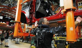 FILE- In this Sept. 27, 2018, file photo United Auto Workers' assemblyman Charles Patterson installs trim on a 2018 Ford F-150 truck on the assembly line at the Ford Rouge assembly plant in Dearborn, Mich. On Friday, Nov. 16, the Federal Reserve reports on U.S. industrial production for October. (AP Photo/Carlos Osorio, File)