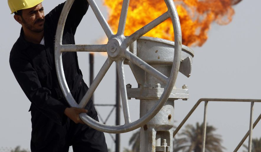 FILE - In this Friday, July 17, 2009, file photo, an Iraqi worker operates valves at the Nahran Omar oil refinery in Zubair near the city of Basra southeast of Baghdad, Iraq. Iraq's Oil Ministry says Iraq has resumed exports from its oil fields around Kirkuk, one year after the city was seized by federal forces from the autonomous Kurdish administration in the north of the country. (AP Photo/Nabil al-Jurani, File)