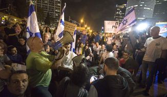 Israeli protesters hold flags and chant slogans during a demonstration against the cease-fire between Israel and Gaza's Hamas in Tel Aviv, Israel, Thursday, Nov. 15, 2018. (AP Photo/Tsafrir Abayov)